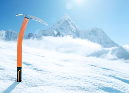 High altitude mountain climber's orange  ICE AXE. It  sticks out in the snow  on snow ice field with Ama Dablam (6812m) summit covered with clouds background.Extremal people vacations concept