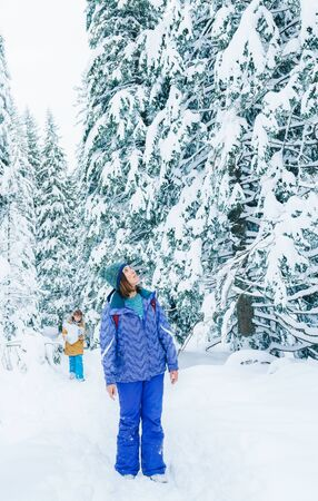 Mother and son have a winter snowy forest walking. Woman standing on the path, rising head up and enjoying the spruces tops.Son have a fun carrying the big snow ball. Winter vacation concept image.