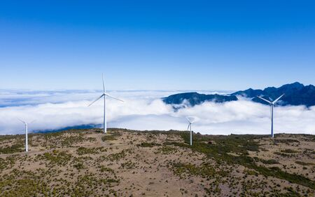 Wind generators with over clouds background and blue sky on clear summer day on the mountain range aerial view, Madeira,Portugal. Green energy concept image.