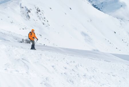 High mountaineer dressed bright orange softshell jacket using a trekking poles ascending the snowy mountain summit. Active people concept image on Velky Krivan, SLovakian Tatry.