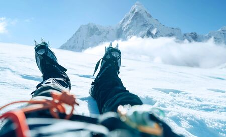 POV shoot of a high altitude mountain climber's lags in crampons. He lying and resting on snow ice field with Ama Dablam (6812m) summit covered with clouds background.Extremal people vacations concept