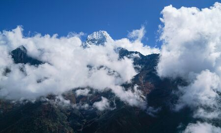Thamserku 6608m mountain summit covered with clouds landscape photo in the eastern Nepal Himalayas. Stock Photo