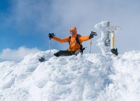 High mountaineer dressed bright orange softshell jacket on the snowy mountain summit.  Active people concept image on Velky Krivan, SLovakian Tatry.