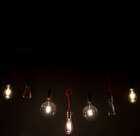 Old vintage light bulb on the wires hanging from the ceiling in the total darkness home decoration background