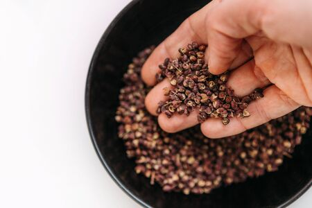 Man's palm taking a scented Sichuan pepper from the bowl on the white table. Sichuan pepper or Chinese pepper or Timur or Nepali pepper is very popular in cuisines of Tibet, Bhutan, Nepal, Thailand.