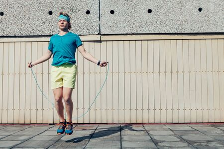Young teenager boy jumping by the skipping rope on the house roof. Modern people fit challenges concept image.