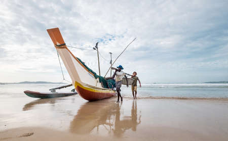 Weligama, Sri Lanka December 21, 2017: Two Fishermen floating on the boat returning home after the night fishing in the morning time. They carrying catch together a  in Weligama, Sri Lanka. Editorial
