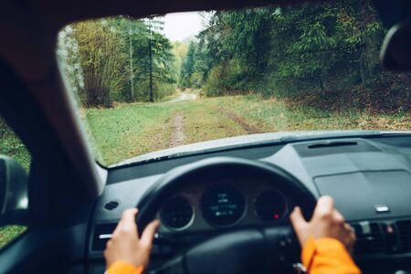 Driver dressed bright orange jacket driving a modern off road left hand drive LHD car on the mountain green forest country road. POV inside car windshield view point. Safely auto driving concept.