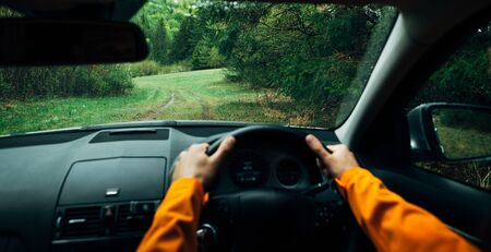 Driver dressed bright orange jacket driving a modern off road right hand drive RHD car on the mountain green forest country road. POV inside car windscreen view point. Safely auto driving concept. Stock Photo