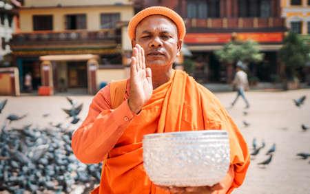 Kathmandu, Nepal - October 20, 2019: Portrait of orange dressed Sadhu old man posing to camera on Boudhanath (Bouddha Stupa) square with a pigeons flock on background in Kathmandu, Nepal. Editorial