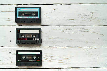 Zilina, - Slovak Republic, May 7, 2020: A image of 3 Compact Cassettes famous Magnetic audio tape manufacturers BASF, JVC and AGFA lying on white wooden table in Zilina city, Slovak Republic