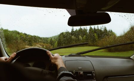 Driver driving a modern off road left hand drive LHD car on the mountain green forest country road at rainy moody day. POV inside car windshield view point. Safely auto driving concept. 스톡 콘텐츠