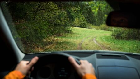 Driver driving a modern off road left hand drive LHD car on the mountain green forest country road. Face reflecting in inside mirror. POV inside car windshield view point. Safely auto driving concept. Stock Photo