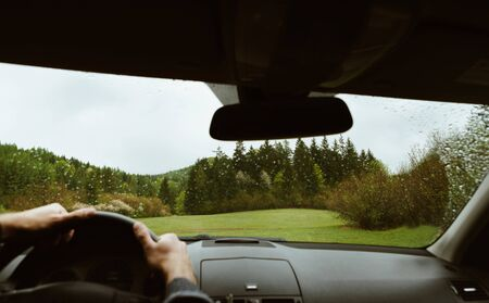 Driver driving a modern off road left hand drive LHD car on the mountain green forest country road at rainy moody day. POV inside car windshield view point. Safely auto driving concept. Stock Photo