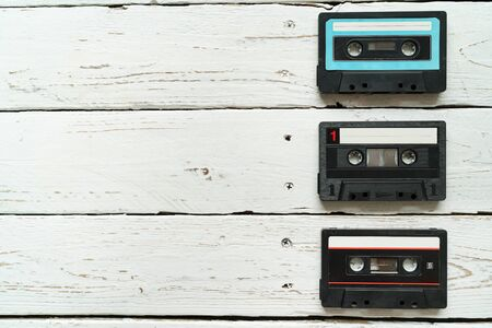 3 Compact Cassettes famous Magnetic audio tape manufacturers lying on white wooden table. Retro and vintage audio music reproduction concept image. Foto de archivo