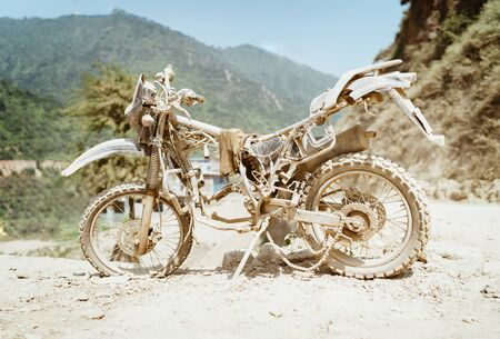 Abandoned old motocross Motorcycle be drowned in deep road dust near the crowed town road in Ramechhap, Nepal. Stock Photo