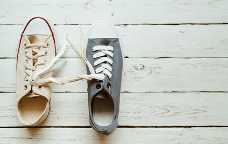 Gray and beige color casual new sneakers intertwined with white shoelaces on the white wooden floor close up image. Love and friendship concept image.