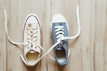 Gray and beige color casual new sneakers intertwined with white shoelaces on the wooden floor close up image. Love and friendship concept image.