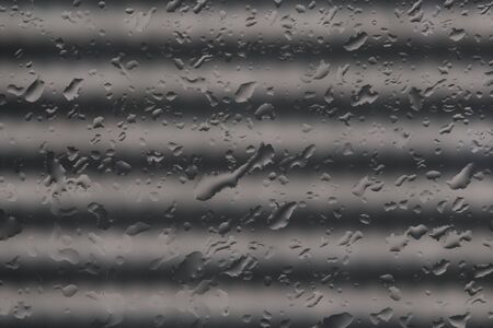 Grey pattern of the water drops with unfocused blurred wave shadows bokeh light on the transparent glass abstract texture.Visual art concept image. Stock Photo