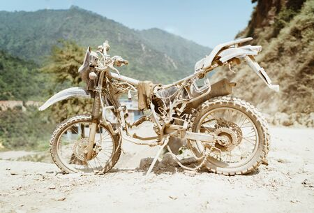 Abandoned old motocross Motorcycle be drowned in deep road dust near the crowed town road in Ramechhap, Nepal. 免版税图像