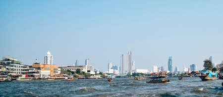 Bangkok, Thailand – February 29, 2019: Thailand capital city Bangkok downtown skyscrapers view from the Chao Phraya river surface with many TAXI service boats and ferries in Bangkok, Thailand Editorial