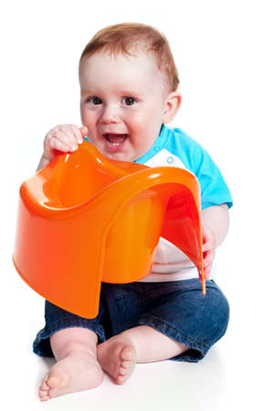 Funny little boy playing with the orange potty studio portrait (isolated on white) Stock Photo