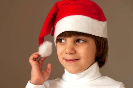 Cute smiling little girl wearing christmas hat studio shot