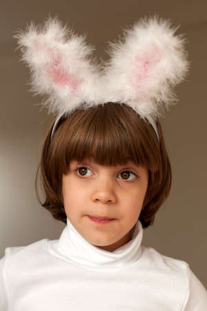 Pretty smiling  little girl wearing bunny ears studio head and shoulders portrait Stock Photo