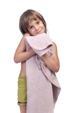 Little girl wearing green shorts, holding pink blanket, studio half length portrait isolated on white background