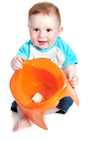 Funny little boy playing with the orange potty studio portrait (isolated on white background) photo