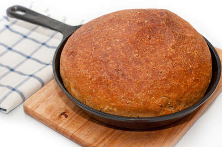 Homemade bread in frying pan on the desk on white background with towel