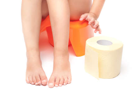 Little child sitting on orange potty and reaching out her hand for the yellow toilet paper