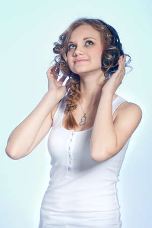 Pretty young girl listening to the music by the headphones studio shot on blue background
