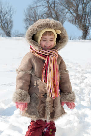 Pretty smiling little girl walking outdoor on the snow field Stock Photo