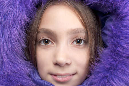 Smiling girl wearing purple fur hood close-up portrait