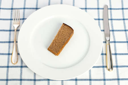 Piece of bread on the plate with fork and knife on tablecloth