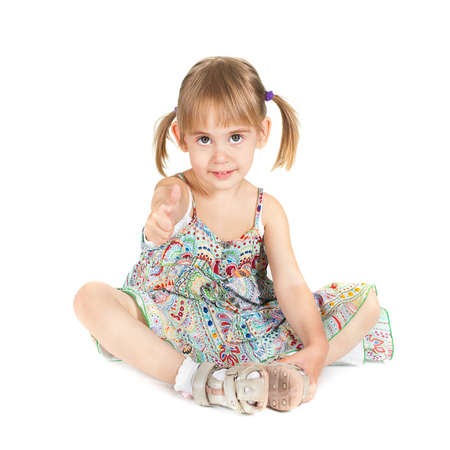 Little girl with big bright eyes and thumb up siting on white background studio shot