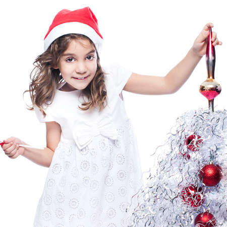 Cute little brunete girl is decorating christmas tree on white background