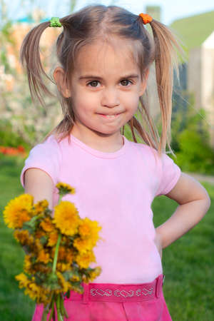 Happy cute little girl  giving flowers to you spring outdoor portrait photo