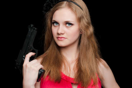 Beautiful girl holding a gun on black background photo