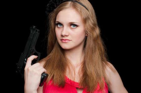 Beautiful girl holding a gun on black background