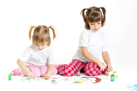 Two little cute girls  sisters  painting  isolated on white background
