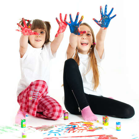 Two little happy beautiful girls  sisters  painting on white background