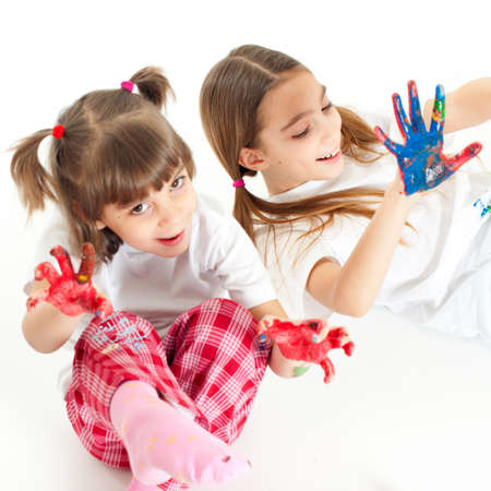 Two little happy beautiful girls  sisters  playing with finger colours on white background