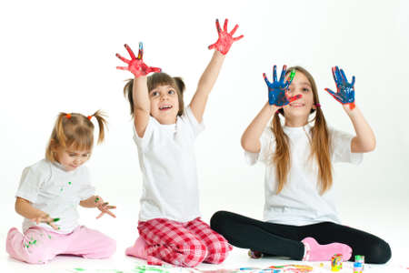 Three little happy beautiful girls (sisters) painting on white background Stock Photo