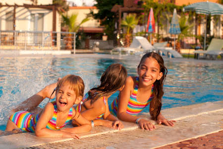 three little girls (sisters) playing and splashing in the pool