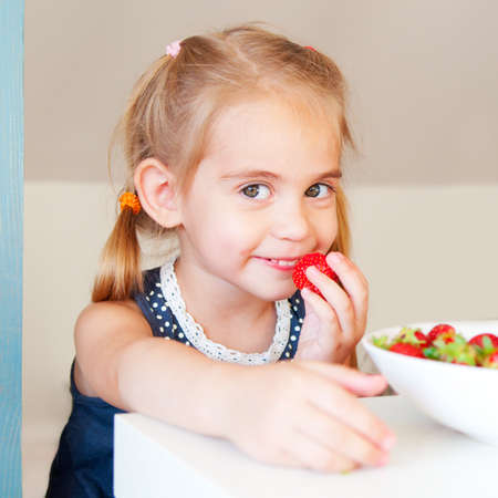 Happy cute little girl eating strawberry