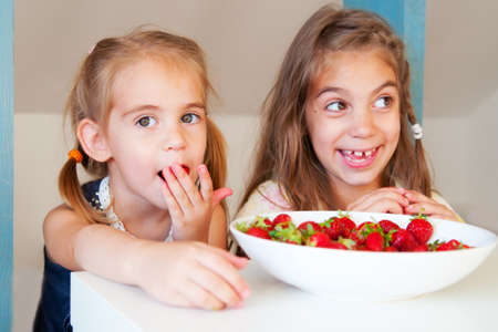 Cute little girls (sisters) eating strawberry Stock Photo