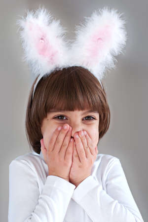 Cute little girl wearing bunny ears close her face with her hands