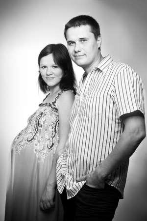 Young caucasian pregnant couple black and white studio portrait
